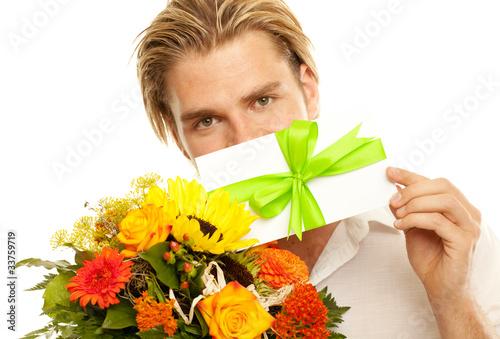attraktiver junger mann mit blumen und gutschein