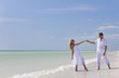 Happy Young Couple Dancing Holding Hands on A Tropical Beach