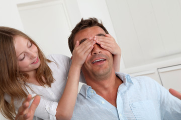 Girl hiding her father's eyes