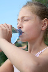 Portrait of young girl drinking water from bottle