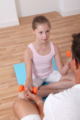 Man helping young girl with fitness exercises
