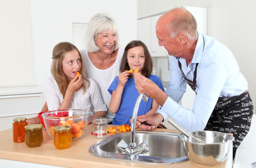 Grandparents cooking with kids in home kitchen
