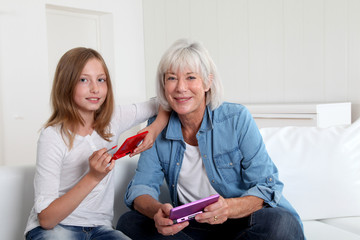 Senior woman and girl playing with gaming console
