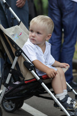 Sad boy in baby carriage