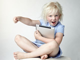 Cute little girl has a lot of fun with her touchpad