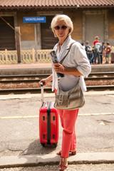 femme retraitée qui attend son train sur le quai de la gare