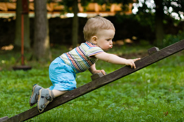 Happy young boy creeping on the ladder in the park