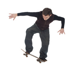 young skateboarder in dark clothes with his skateboard