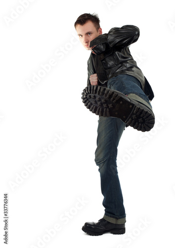 kicking serious young man in leather jacket