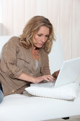 Woman typing at a laptop computer at home