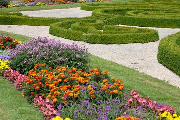 Gartenanlage mit Buchs, Kiesel und Blumen