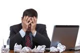 Fototapety Mann sitzt verzweifelt über Papierflut am Arbeitsplatz