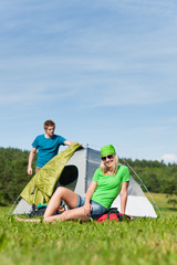 Camping couple build-up tent sunny countryside