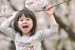 桜の下で声を出している女の子