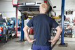 Rear view mechanic looking at car
