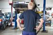 Rear view mechanic looking at car