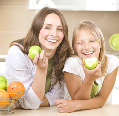 Happy Mother with Daughter eating Healthy food. Diet