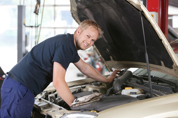 Smiling mechanic working on car