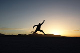 Silhouette of jumping man at sunset