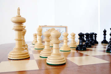 Chess pieces on wood board, black and white