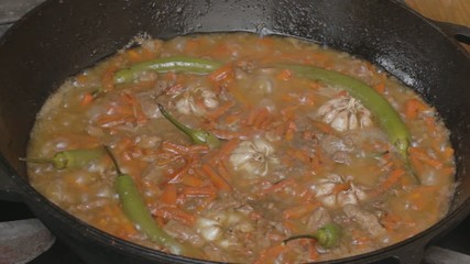 EDIT Pepper, garlic, carrot and pork stewing in cauldron.