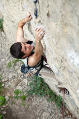 Rock climber battling his way up