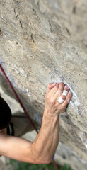 Rock climber's hand grasping handhold on cliff