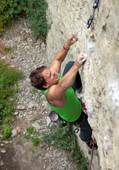 Rock climber struggling to reach next handhold