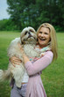 Pretty casual woman with cute little shih tzu dog outdoors in a
