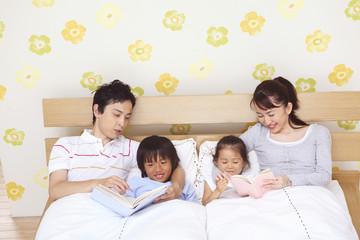 子供を寝かしつける両親