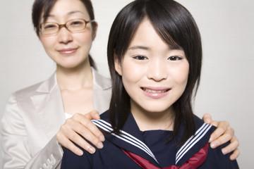 女子中学生の肩を後ろから持つ塾講師