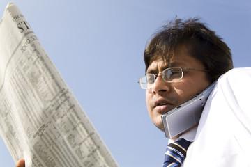 新聞を見ながら電話するビジネスマン