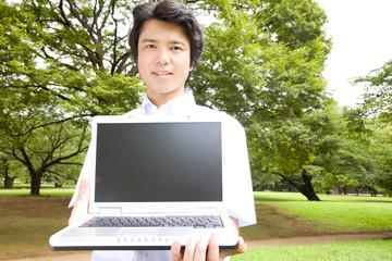 ノートパソコンのモニターを見せるビジネスマン