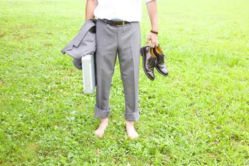裸足で芝生に立つビジネスマンの下半身