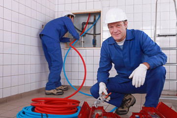 two plumbers working, one plumber is connecting pipes