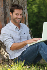Smiling man sitting with laptop computer in the park