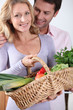 Husband looking at wife with vegetable basket.