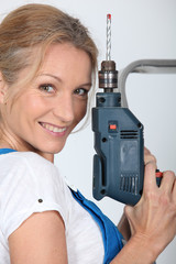 Closeup of smiling lady with electric drill