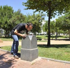 Chico bebiendo agua en fuente del parque
