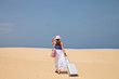 Woman walking with luggage on a sand to the sea