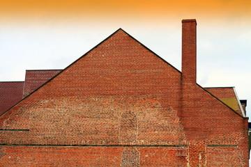 edificio di mattoni con lungo comignolo e senza finestre