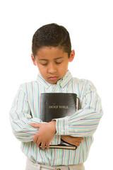 Child Praying While Embracing Bible