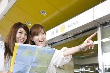 空港で地図を確認する2人の女性