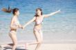 浜辺を駆ける水着を着た2人の女性