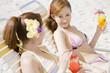 浜辺でデッキチェアに座ってトロピカルジュースを飲んでいる女性2人