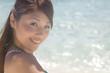 波打ち際で振り返る笑顔の水着女性
