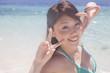 波打ち際で記念撮影を撮る水着女性