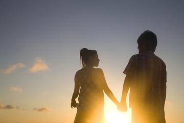 夕暮れに手を繋ぐカップルのシルエット