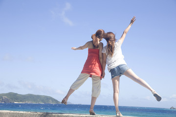 海の方に手を振る女性2人