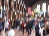 A motion and lens burred image of people travelling poster